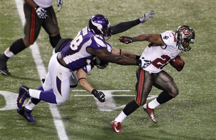 Tampa Bay Buccaneers running back Doug Martin (22) breaks a tackle by Minnesota Vikings defensive tackle Letroy Guion (98) during a 64-yard touchdown reception in the second half of an NFL game Thursday, Oct. 25, 2012, in Minneapolis. The Buccaneers won 36-17. (AP Photo/Andy King)