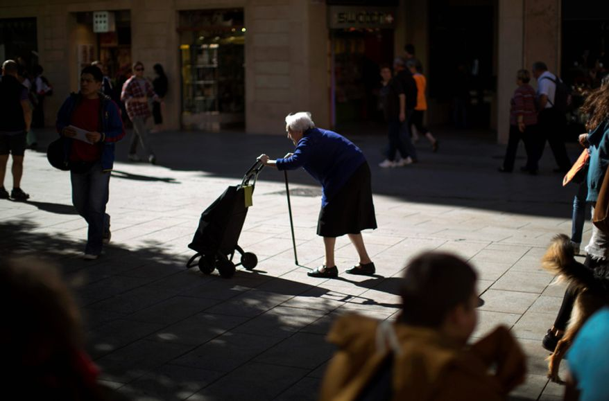 A woman pushes her shopping cart along a street in Barcelona on Tuesday, Oct. 16, 2012. Spain has raised 4.9 billion euros ($6.4 billion) at slightly lower interest rates in a debt auction that saw strong demand as the country considers whether to request international help to manage its finances. (AP Photo/Emilio Morenatti)