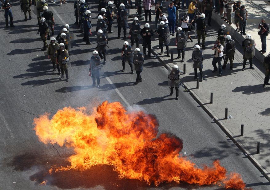 Protesters throw gasoline bombs at riot police during a 24-hour nationwide general strike in Athens on Thursday, Oct. 18, 2012. Greece faced its second general strike in a month as workers protested over another batch of austerity measures that are designed to prevent the bankruptcy of the country. (AP Photo/Thanassis Stavrakis)