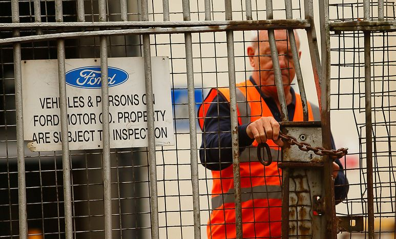 A security guard locks a gate at the Ford Transit Assembly Plant in Southampton, England, after workers were told the site will close, with the loss of up to 1,500 jobs, on Thursday, Oct. 25, 2012. Ford, which expects to lose more than $1 billion a year in Europe, has been pursuing plant closures and layoffs. (AP Photo/Chris Ison/PA)