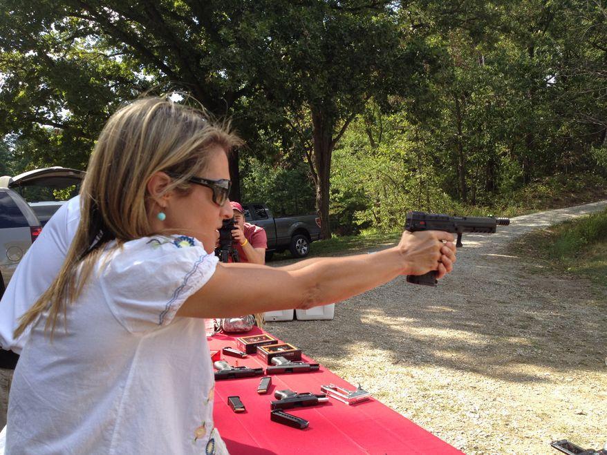 Emily Miller shooting a .22 caliber pistol.