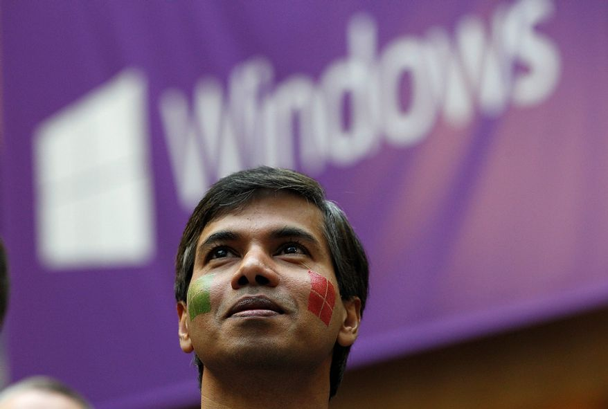 Microsoft program manager Joseph Morris, sporting a pair of company temporary-tattoo logos on his face, looks on during an event unveiling a new Microsoft Windows operating system Thursday, Oct. 25, 2012, at the company's headquarters in Redmond, Wash. Though Windows 8 will be backed by a $1 billion marketing campaign, questions surround the software. The biggest one of all: Is it innovative and elegant enough to lure consumers who've fallen in love with an assortment of smartphones, tablet computers and other gadgets? (AP Photo/Elaine Thompson)