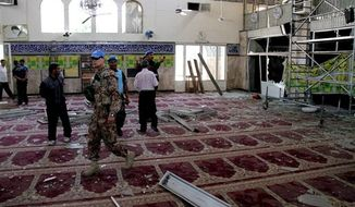 ** FILE ** In this June 14, 2012, file photo, U.N. observers inspect the prayer hall of the Sayyida Zeinab shrine, which was damaged after a car bomb exploded near the shrine, in a suburb of Damascus, Syria. Iraqi Shiites increasingly fear the Muslim sect and its holy sites could be targeted in Syria, and Iranian-linked militants loyal to the faction are girding for a new eruption of retaliatory sectarian fighting, according to Iraqi Shiite leaders and government officials. (AP Photo/Bassem Tellawi, File)