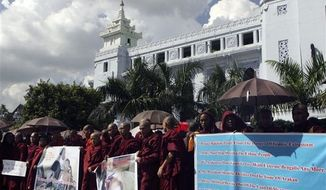 Myanmar Buddhist monks hold banners and placards during a rally against recent violence in Rakhine state, outside the city hall in Yangon, Myanmar, Thursday, Oct. 25, 2012. Nearly 200 protesters including Buddhist monks called for the stop of renewed violence in western coast of Myanmar. (AP Photo)