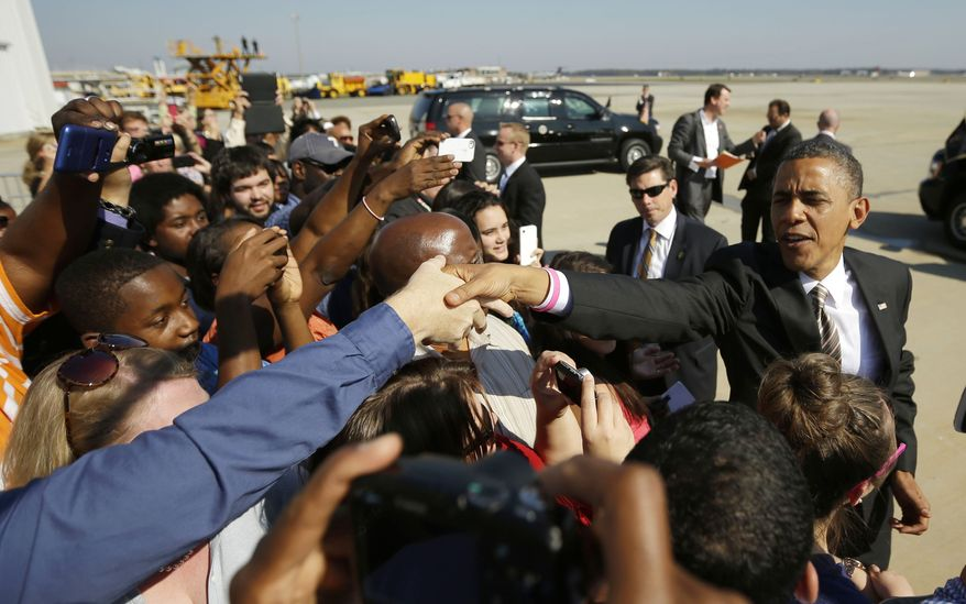 President Obama reaches over to greets supporters on the tarmac upon his arrival Oct. 25, 2012, on Air Force One at Richmond International Airport in Richmond, Va. (Associated Press)