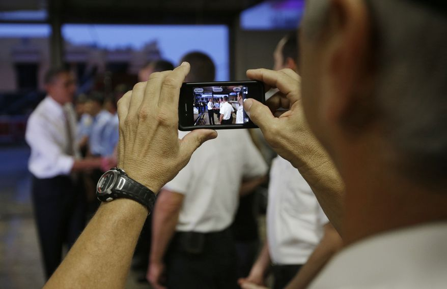 A firefighter takes a picture of President Obama shaking hands with his co-workers Oct. 25, 2012, during an unannounced visit by the president to Fire Station No. 14 in Tampa, Fla. Obama had purchased doughnuts nearby and delivered them to the firefighters before heading off to a campaign event. (Associated Press)