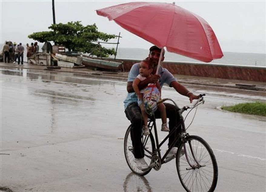 A man balances a child and umbrella on his bike as it rains during the approach of Hurricane Sandy in Manzanillo, Cuba, Wednesday, Oct. 24, 2012. (AP Photo/Franklin Reyes)