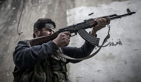 In this Wednesday, Oct. 24, 2012 photo. An Free Syrian Army fighter shoots his gun towards government troops as rebel fighters belonging to the Liwa Al Tawhid group carry out a military operation at the Moaskar front line, one of the battlefields in Karmal Jabl neighborhood, in Aleppo, Syria. (AP Photo/Narciso Contreras).