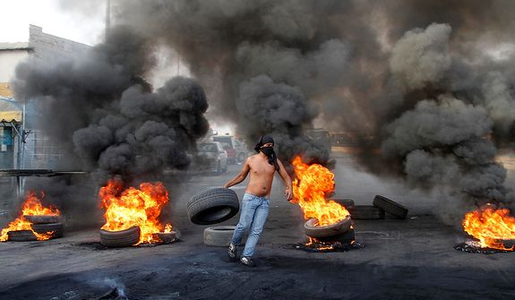 A masked protester carried a tire to add to burning tires used as a roadblock to protest the death of Brig. Gen. Wissam al-Hassan, head of the intelligence division of Lebanon's domestic security forces in a car bomb attack targeting his convoy, in the southern port city of Sidon, Lebanon, Saturday, Oct. 20, 2012. Protesters burned tires and set up roadblocks around Lebanon on Saturday in a sign of boiling anger over a massive car bomb that killed a top security official and seven other people a day earlier ó a devastating attack that threatened to bring Syria's civil war to Lebanon.(AP Photo/ Mohammed Zaatari)
