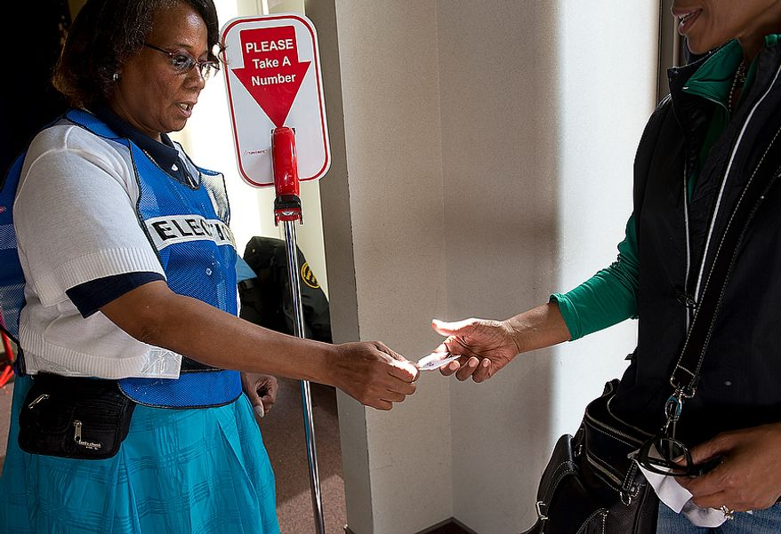 Voter assistance clerk Sheila Washington hands out numbers to early voters at Judiciary Square in Washington on Wednesday, Oct. 24, 2012. According to site officials, some 2,400 people have voted here since Monday, when the voting opened. The District of Columbia will open seven more early-voting sites on Saturday (one in each ward), which will be open daily except Sundays until Nov. 3 from 8:30 a.m. to 7 p.m. (Barbara L. Salisbury/The Washington Times)