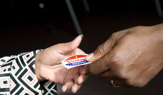 """A voter collects her """"I Voted Today"""" sticker after voting early at Judiciary Square in Washington on Wednesday, Oct. 24, 2012. According to site officials, some 2,400 people have voted here since Monday, when the voting opened. The District of Columbia will open seven more early-voting sites on Saturday (one in each ward), which will be open daily except Sundays until Nov. 3 from 8:30 a.m. to 7 p.m. (Barbara L. Salisbury/The Washington Times)"""