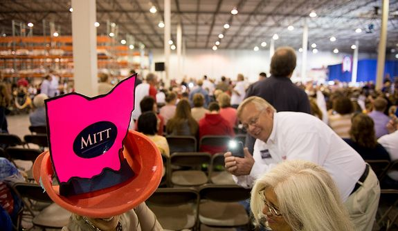 Julie McCormick of Cincinnati, Ohio, left, smiles as Mitt Romney supporters photograph her in a big hat with a cut out of the state of Ohio taped to it before Romney speaks at a campaign stop at Jet Machine, a small business military manufacturing company, Cincinnati, Ohio, Thursday, October 25, 2012. Since the Iraq war and Afghanistan war draw down Jet Machine has gone from 160 employees to 115 employees and has begun shifting into manufacturing for oil drilling and hydraulic fracturing. (Andrew Harnik/The Washington Times)