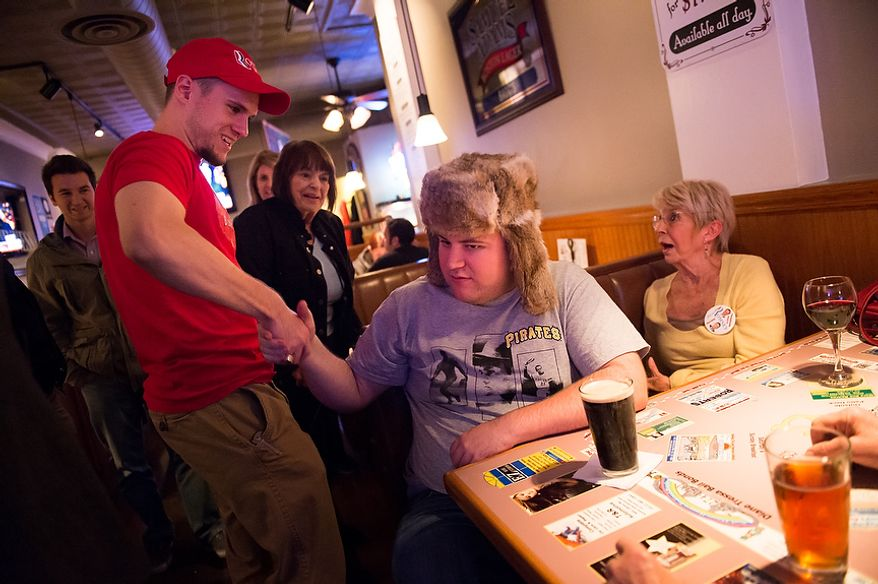 Romney campaign volunteers Harrison Moder, second from left, of Mt. Lebanon, greets Griffin Emerson, second from right, and Gloria Leonard, right, of Pittsburgh, Pa., as Romney supporters arrive for a presidential debate watch party at Bados Pizza Grill and Ale House, Mt. Lebanon, Pa., Monday, October 22, 2012. (Andrew Harnik/The Washington Times)