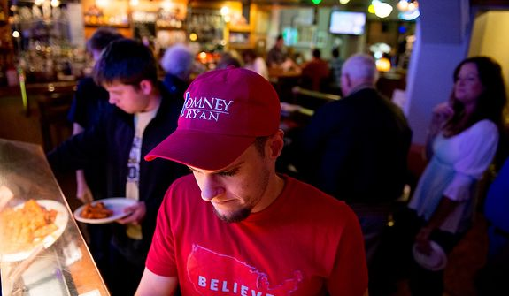 Romney campaign volunteer Harrison Moder, center, of Mt. Lebanon, gather with fellow Romney supporters for a presidential debate watch party at Bados Pizza Grill and Ale House, Mt. Lebanon, Pa., Monday, October 22, 2012. (Andrew Harnik/The Washington Times)