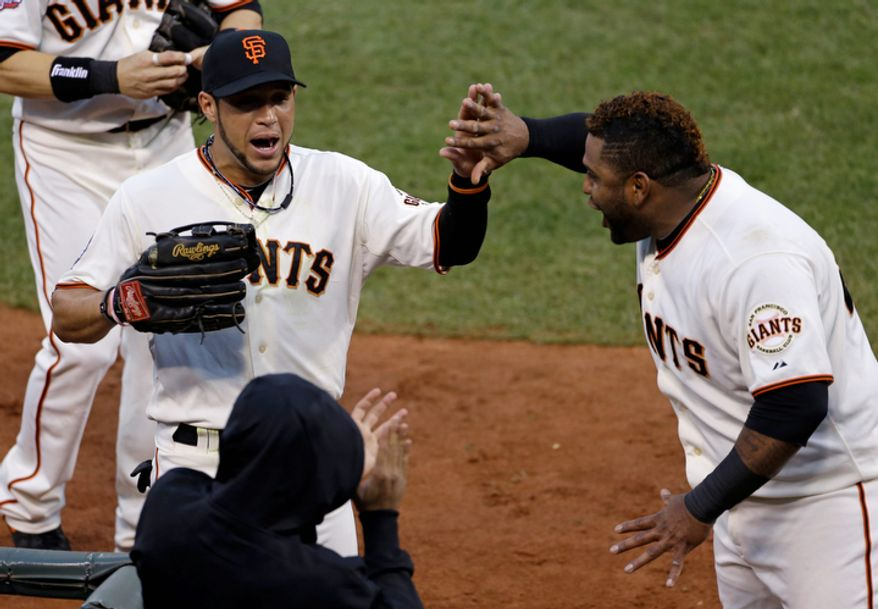 San Francisco Giants LF Gregor Blanco (left) is congratulated by teammate Pablo Sandoval after making a diving catch in the third inning of Game 1 of the World Series between the Giants and Detroit Tigers in San Francisco on Oct. 24, 2012. (Associated Press)