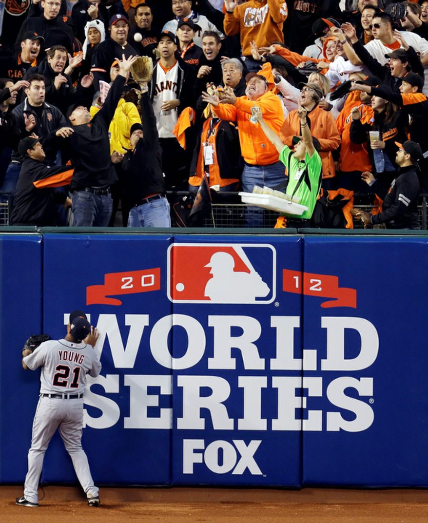 Detroit Tigers LF Delmon Young can only watch as fans go after a two-run home run ball hit by San Francisco Giants 3B Pablo Sandoval during the third inning of Game 1 of the World Series in San Francisco on Oct. 24, 2012. (Associated Press)