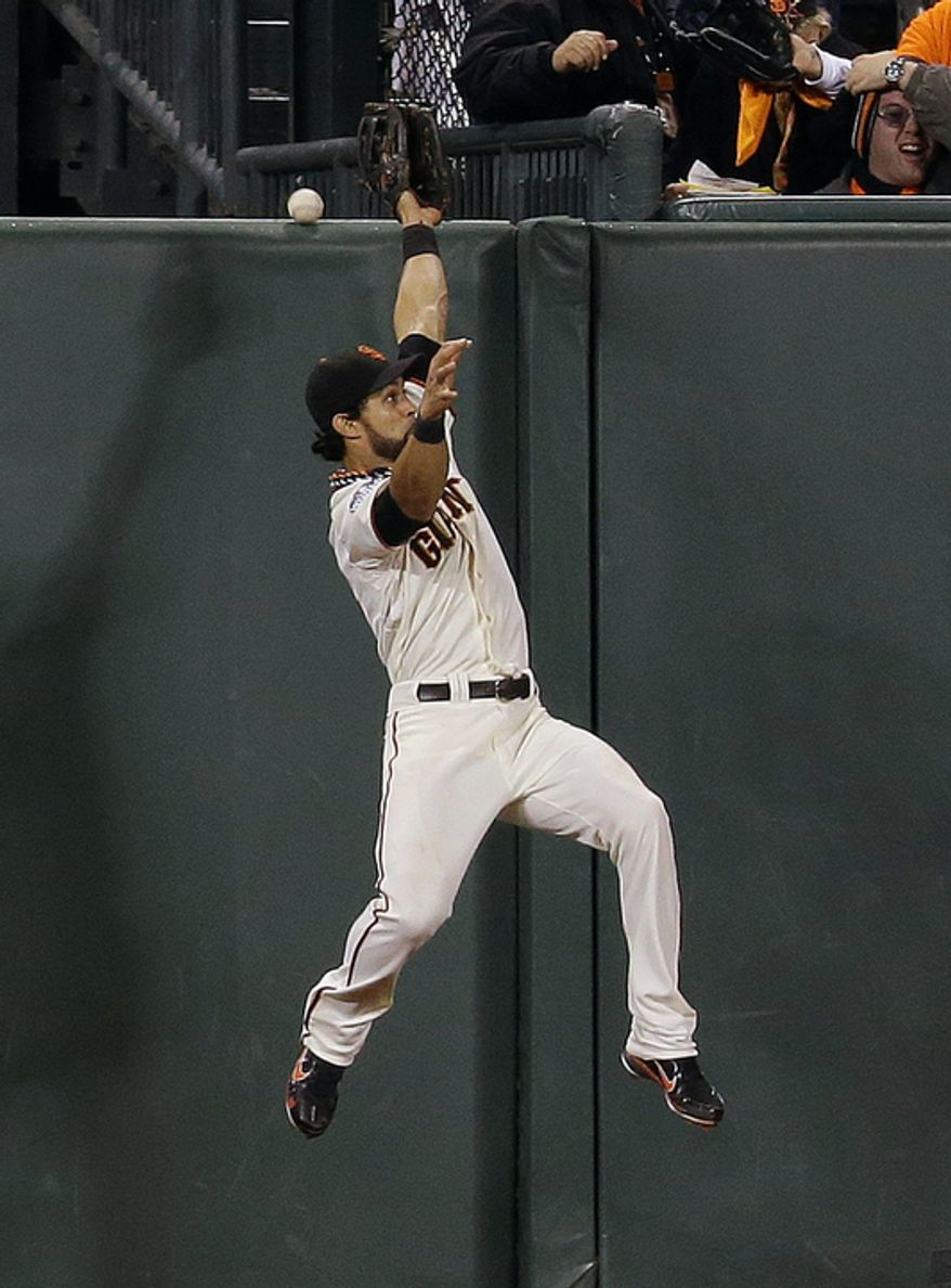 San Francisco Giants CF Angel Pagan unsuccessfully tries to catch a two-run home run by Detroit Tigers SS Jhonny Peralta during the ninth inning of Game 1 of the World Series in San Francisco on Oct. 24, 2012. (Associated Press)