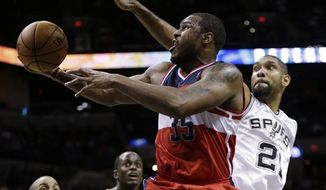 Washington Wizards' Trevor Booker (35) shoots as San Antonio Spurs' Tim Duncan (21) defends during the third quarter of an preseason NBA basketball game, Friday, Oct. 26, 2012, in San Antonio. (AP Photo/Eric Gay)