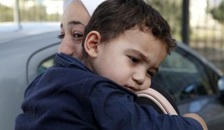 Bushr Al Tawashi is carried by his mother, Arin Al Dakkar, outside of a private Sigma TV station in Nicosia, Cyprus, on Oct. 26, 2012. The 2-year-old Syrian boy, who was believed dead after his family inadvertently left him behind as they fled shelling in Damascus last summer, was been reunited with his parents in Cyprus, a lawyer said. (Associated Press)