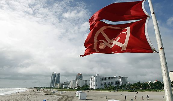 Red flags fly from a lifeguard station as Hurricane Sandy passes offshore to the east, Friday, Oct. 26, 2012, in Miami Beach, Fla. Hurricane Sandy left at least 21 people dead as it moved through the Caribbean, following a path that could see it blend with a winter storm and reach the U.S. East Coast as a super-storm next week. (AP Photo/Lynne Sladky)