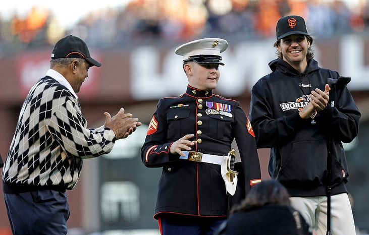 Willie Mays (left) and San Francisco Giants pitcher Barry Zito (right) wait as Marine Cpl. Nick Kimmel throws out the ceremonial first pitch before Game 2 of the World Series between the Giants and Detroit Tigers in San Francisco on Oct. 25, 2012. (Associated Press)