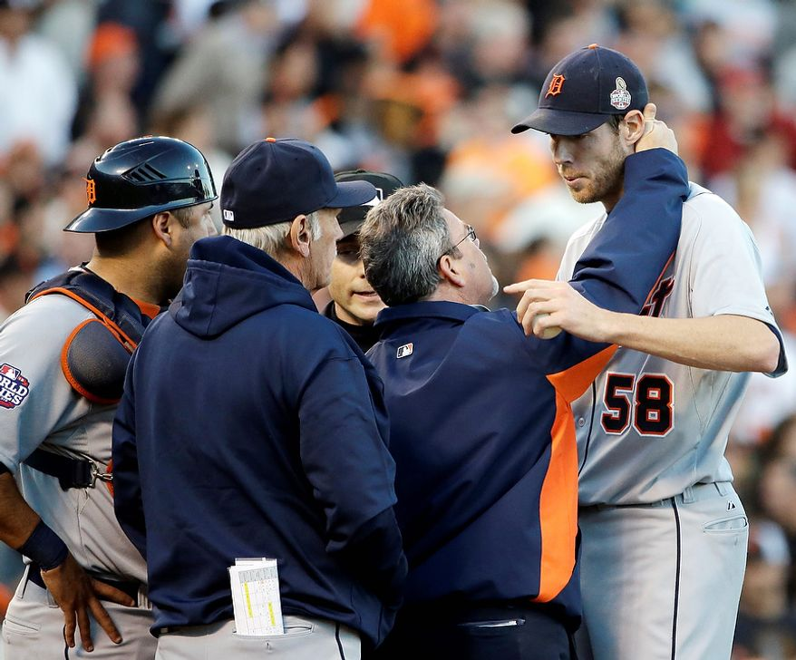 Detroit Tigers starting pitcher Doug Fister is examined by a trainer after getting hit in the head by a line drive during the second inning of Game 2 of the World Series between the Tigers and San Francisco Giants in San Francisco on Oct. 25, 2012. (Associated Press)