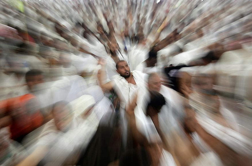 "In this image made while zooming the camera lens, Muslim pilgrims cast stones at a pillar, symbolizing the stoning of Satan, in a ritual called ""Jamarat,"" a rite of the annual hajj, the Islamic faith's most holy pilgrimage, in Mina near the Saudi holy city of Mecca, Saudi Arabia, on Oct. 26, 2012. The five-day rituals of Hajj began on Oct. 24 when millions arrived in the holy city. (Associated Press)"