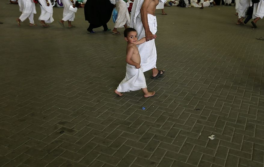 """Youssef, 3, a Muslim pilgrim from Egypt, walks with his grandfather to cast stones at a pillar, symbolizing the stoning of Satan, in a ritual called """"Jamarat,"""" the last rite of the annual hajj, in Mina near the Saudi holy city of  Mecca, Saudi Arabia, on Oct. 26, 2012. (Associated Press)"""