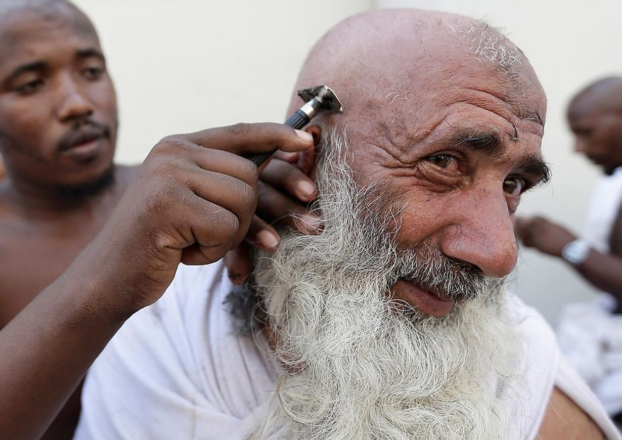 """A Muslim pilgrim has his head ritually shaved after he cast stones at a pillar, symbolizing the stoning of Satan, in a ritual called """"Jamarat,"""" a rite of the annual hajj, the Islamic faith's most holy pilgrimage, in Mina near the Saudi holy city of Mecca, Saudi Arabia, on Oct. 26, 2012. The five-day rituals of Hajj began on Oct. 24 when millions arrived in the holy city. (Associated Press)"""