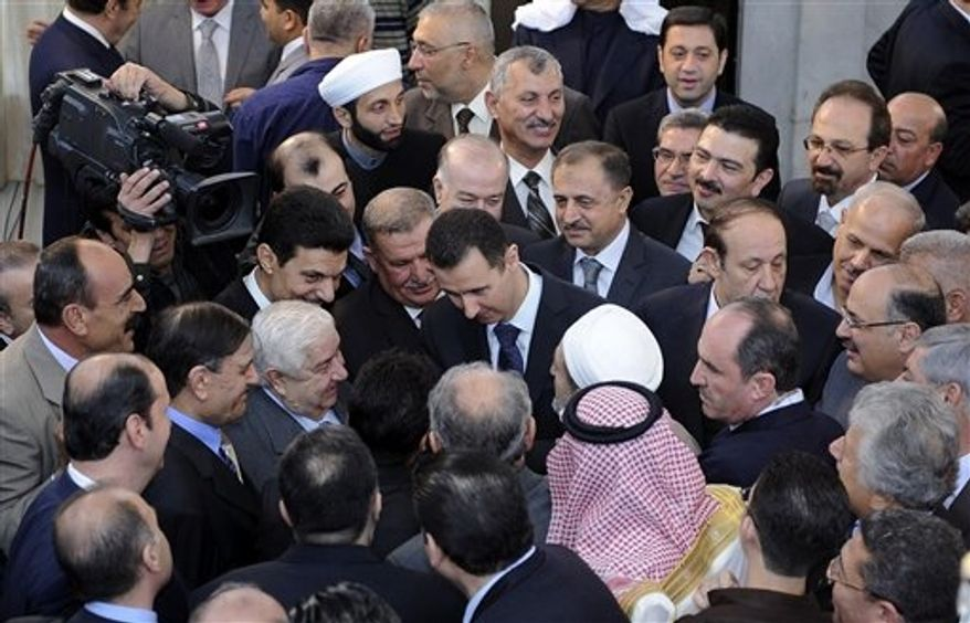 In this photo released by the Syrian official news agency SANA, Syrian President Bashar Assad, center, shakes hands with worshippers at a mosque on the first day of Eid al-Adha, Friday, Oct. 26, 2012. Fighting raged near a military base in Syria's north as a cease-fire in the bloody civil war was supposed to go into effect Friday at dawn, activists said, illustrating the difficulty of enforcing even a limited truce coinciding with a Muslim holiday. (AP Photo/SANA)
