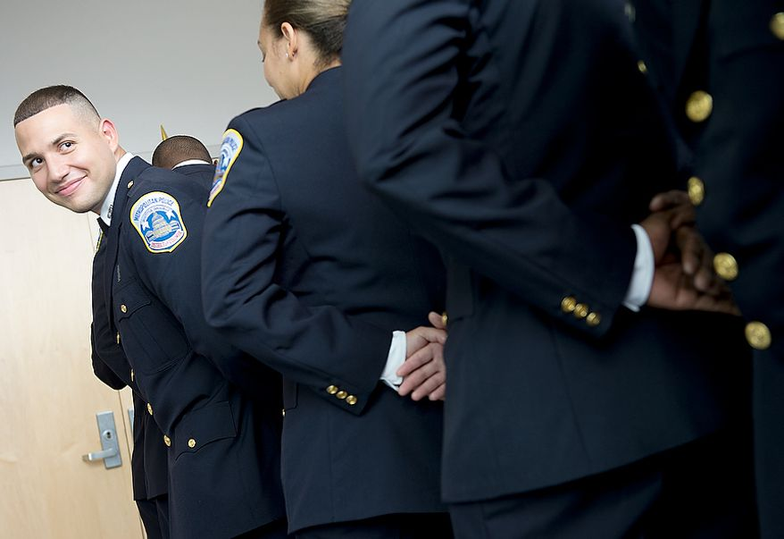 Guillermo Canales looks back at fellow members of Metropolitan Police Department's recruit class 2012-3 as they stand in line to process for their graduation on Oct. 26, 2012, at the Metropolitan Police Academy in Southwest Washington. (Barbara L. Salisbury/The Washington Times)