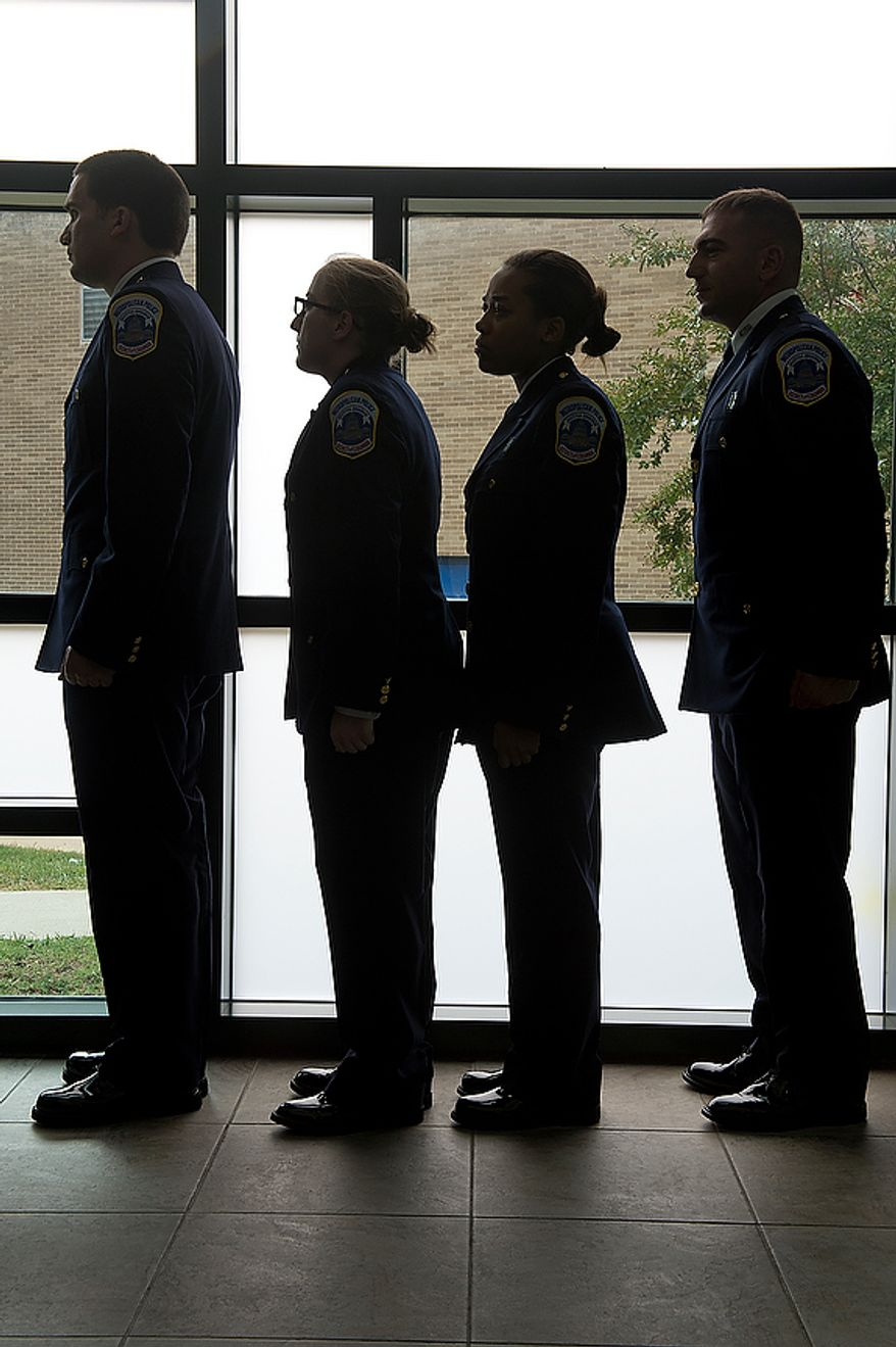 Members of Metropolitan Police Department's recruit class 2012-3 stand in line as they wait to process for their graduation Oct. 26, 2012, at the Metropolitan Police Academy in Southwest Washington. (Barbara L. Salisbury/The Washington Times)