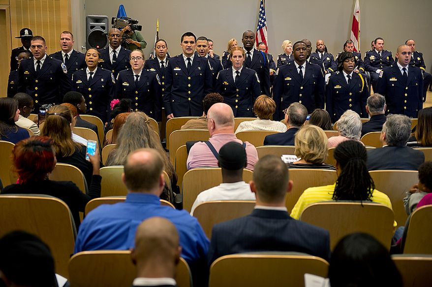 The 15 new officers from Metropolitan Police Department's recruit class 2012-3 stand to face family and friends in the audience as they recite their oath of office during their graduation ceremony on Oct. 26, 2012, at the Metropolitan Police Academy in Southwest Washington. (Barbara L. Salisbury/The Washington Times)