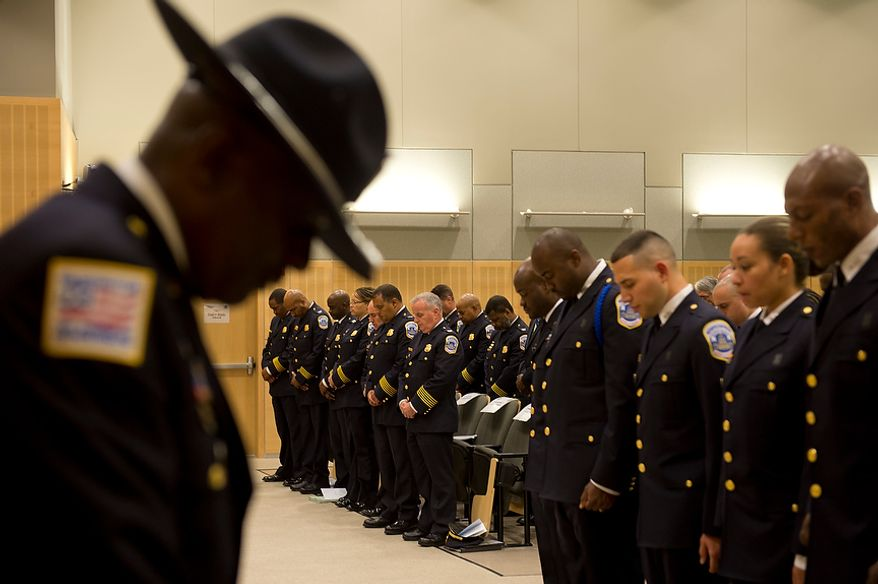 Police officers bow their heads in prayer at the graduation ceremony for Metropolitan Police Department's recruit class 2012-3 on Oct. 26, 2012, at the Metropolitan Police Academy in Southwest Washington. (Barbara L. Salisbury/The Washington Times)