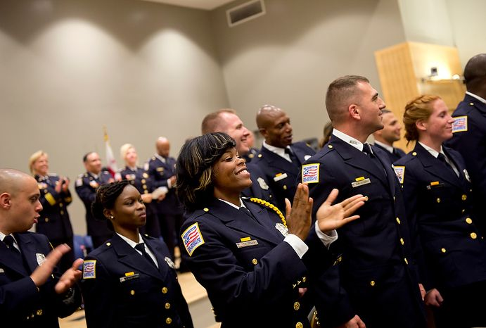 Officers, including class leader Tiffany Green (center), applaud following their induction as new police officers in the Metropolitan Police Department on Oct. 26, 2012. (Barbara L. Salisbury/The Washington Times)
