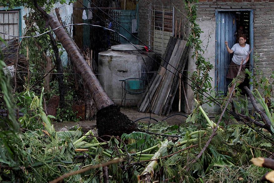 A woman stands at the entrance of her house in front of a fallen palm tree after the passing of Hurricane Sandy in Santiago de Cuba, Cuba, on Oct. 25, 2012. Hurricane Sandy blasted across eastern Cuba on Thursday as a potent Category 2 storm and headed for the Bahamas after causing at least two deaths in the Caribbean. (Associated Press)