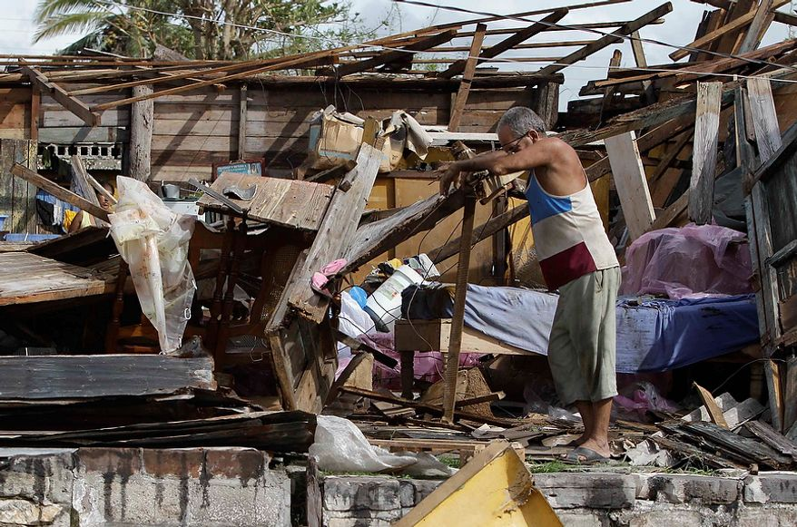 Resident Antonio Garces tries to recover his belongings from his house, destroyed by Hurricane Sandy, in Aguacate, Cuba, on Oct. 25, 2012. Hurricane Sandy blasted across eastern Cuba as a potent Category 2 storm and headed for the Bahamas after causing at least two deaths in the Caribbean. (Associated Press)