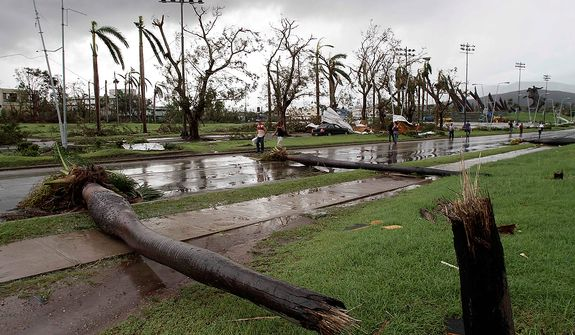Fallen palm trees lie on a road in Santiago de Cuba, Cuba, on Oct. 25, 2012, after Hurricane Sandy blasted across eastern Cuba as a potent Category 2 storm and headed for the Bahamas after causing at least two deaths in the Caribbean. (Associated Press)