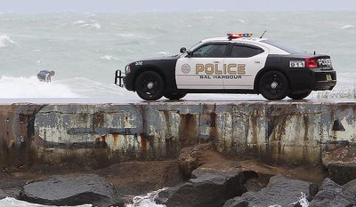 A surfer (rear left) takes advantage of waves produced by Hurricane Sandy's outer bands at Haulover Beach in Miami as the Bal Harbour police patrol the area on Oct. 25, 2012. (Associated Press/El Nuevo Herald)