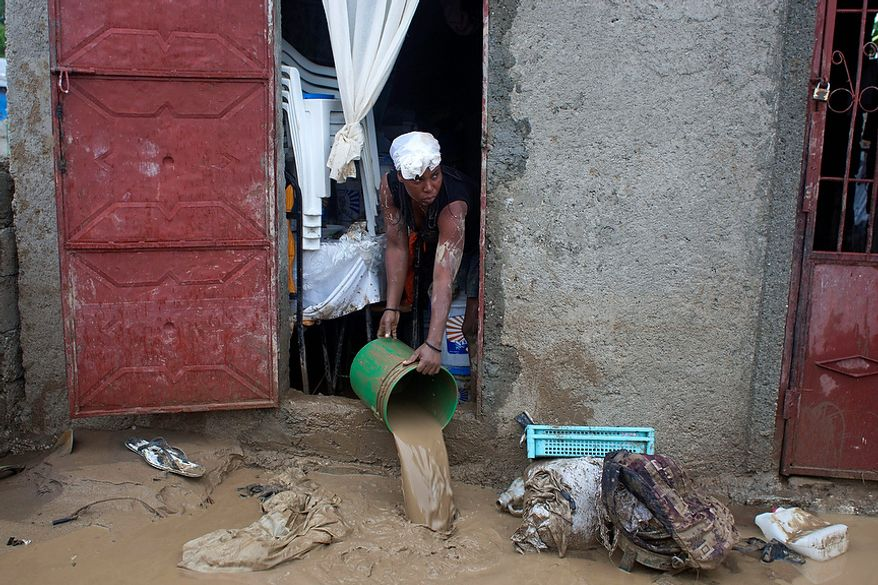 A resident drains mud from a flooded house after heavy rains brought by Hurricane Sandy in Port-au-Prince, Haiti, on Oct. 25, 2012. Sandy was blamed for the death of an elderly man in Jamaica who was crushed by a boulder. Another man and two women died while trying to cross storm-swollen rivers in southwestern Haiti. (Associated Press)