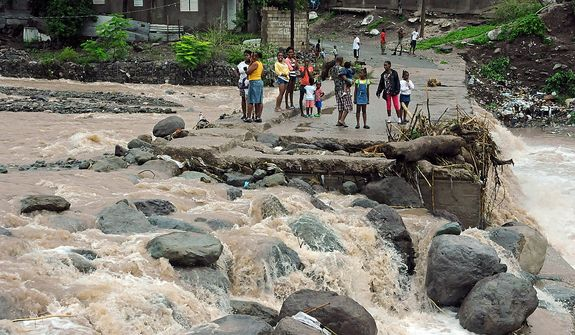 Residents stand Oct. 25, 2012, on a bridge that was previously destroyed in 2008 by Tropical Storm Gustav, while watching Hope River swell in the village of Kintyre, near Kingston, Jamaica, after the passing of Hurricane Sandy. (Associated Press)