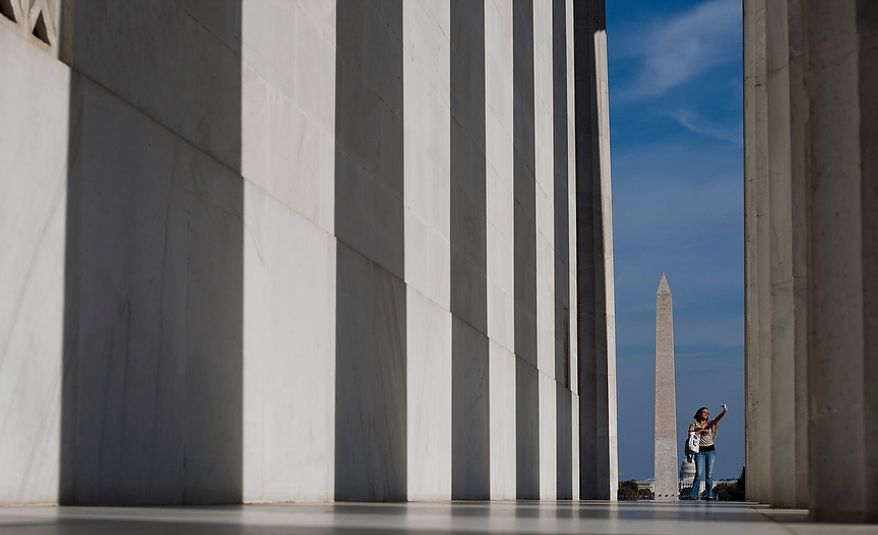 A tourist takes photos along the outer edge of the Lincoln Monument with the Washington Monument and Capital in the background, Washington, D.C., Wednesday, Oct. 17, 2012. (Craig Bisacre/The Washington Times)
