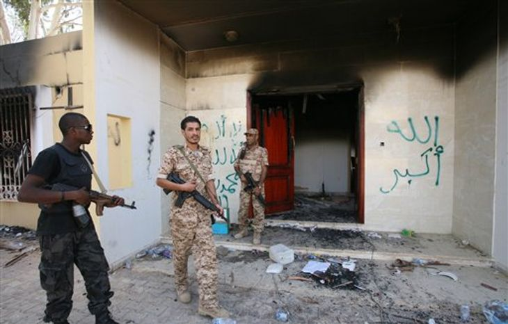 In this Sept. 14, 2012, file photo, Libyan military guards check one of the burnt out buildings at the U.S. Consulate in Benghazi, Libya, during a visit by Libyan President Mohammed el-Megarif to express sympathy for the death of U.S. Ambassador to Libya J. Christopher Stevens and his colleagues in the Sept. 11, 2012, attack on the consulate. (AP Photo/Mohammad Hannon, File)