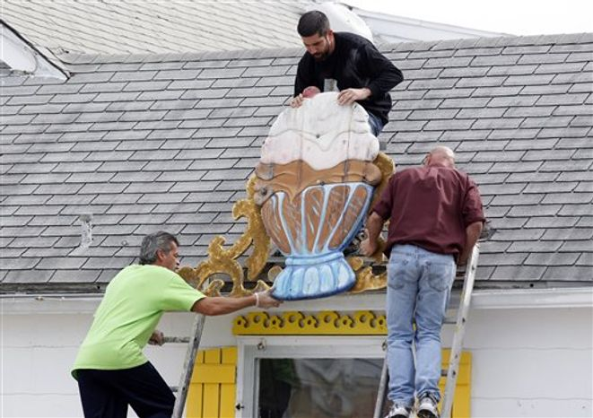 Jerry Velez, top, Richard Caguilat, left, and William Disburger, right, remove a large sign from the Sea Shell Ice Cream shop in Wildwood, N.J., Saturday, Oct. 27, 2012, in preparation for Hurricane Sandy. From the lowest lying areas of the Jersey shore, where residents were already being encouraged to leave, to the state's northern highlands, where sandbags were being filled and cars moved into parking lots on high ground, New Jersey began preparing in earnest for Hurricane Sandy. (AP Photo/Mel Evans)