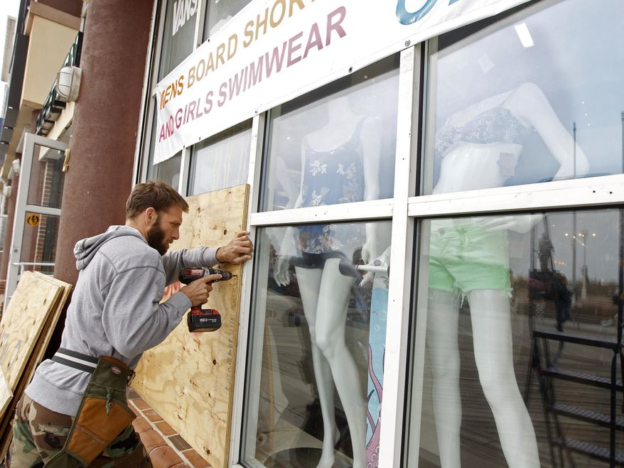 A worker boards up the windows of the store as Hurricane Sandy approaches in Ocean City, Md., on Saturday, Oct. 27, 2012. (AP Photo/Jose Luis Magana)