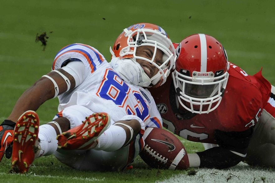 Florida wide receiver Solomon Patton (83) is tackled by Georgia safety Shawn Williams (36) during the first half of an NCAA college football game, Saturday, Oct. 27, 2012 in Jacksonville, Fla. Patton left the game after the play with a broken arm. Georgia beat Florida 17-9. (AP Photo/Stephen Morton)