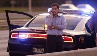 Sen. Marco Rubio, R-Fla., who is traveling with Republican presidential candidate and former Massachusetts Gov. Mitt Romney, uses a phone as he stands alongside Interstate 4 in Lakewood Crest, Fla., Saturday, Oct. 27, 2012, after the motorcade was stopped. The 12-year-old daughter of Sen. Rubio had been airlifted to a hospital after a Saturday motor vehicle accident. (AP Photo/Charles Dharapak)