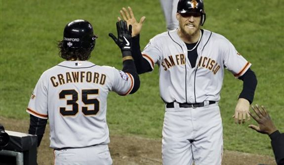 San Francisco Giants' Hunter Pence is congratulated by Brandon Crawford (35) after scoring during the second inning of Game 3 of baseball's World Series against the Detroit Tigers Saturday, Oct. 27, 2012, in Detroit. (AP Photo/Paul Sancya )