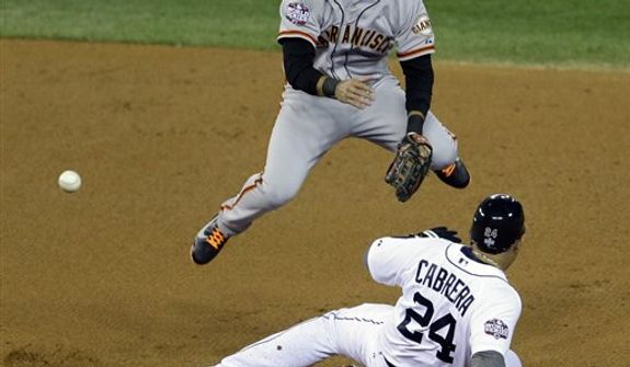 San Francisco Giants shortstop Brandon Crawford leaps over Detroit Tigers' Miguel Cabrera (24) to turn a double play on a ball hit by Prince Fielder during the first inning of Game 3 of baseball's World Series Saturday, Oct. 27, 2012, in Detroit. (AP Photo/Paul Sancya )