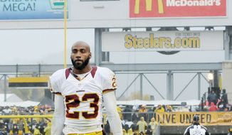 With an image of him arguing with an official in the background, Redskins cornerback DeAngelo Hall walks off the field after being ejected in the fourth quarter of Sunday's loss. (Preston Keres/Special to The Washington Times)